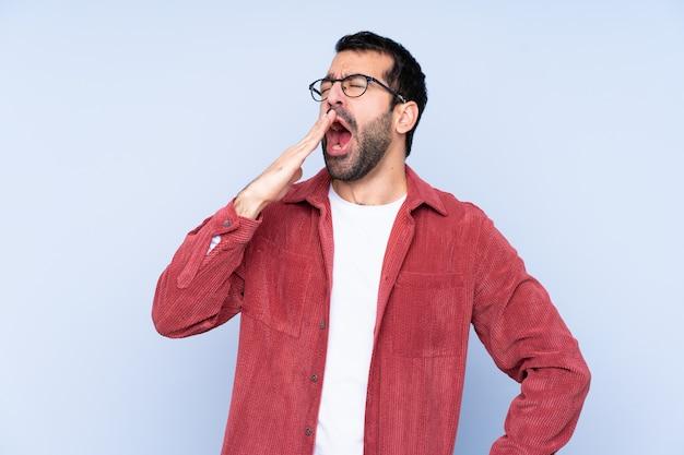 あくびと手で口を大きく開けてカバーする青い壁にコーデュロイジャケットを着ている若い白人男