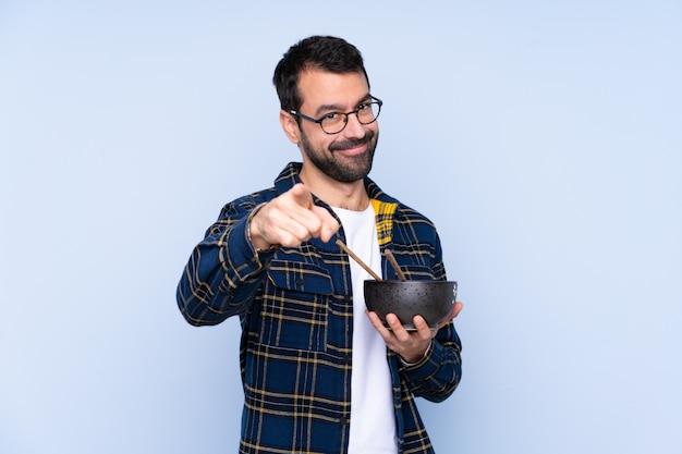 Молодой кавказский человек над синей стеной уверенно показывает на тебя пальцем, держа миску лапши с палочками для еды