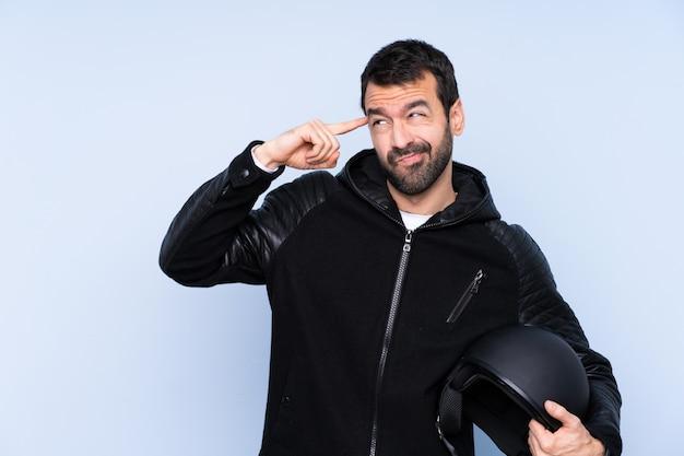 頭に指を置いて狂気のジェスチャーを作る孤立した壁の上のオートバイのヘルメットを持つ男