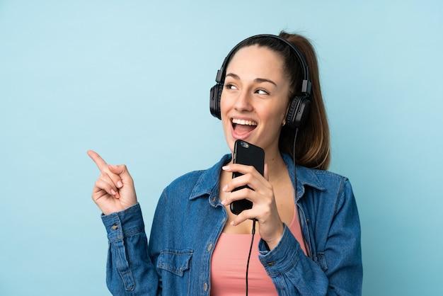 携帯電話と歌で音楽を聴く分離の青い壁の上の若いブルネットの女性