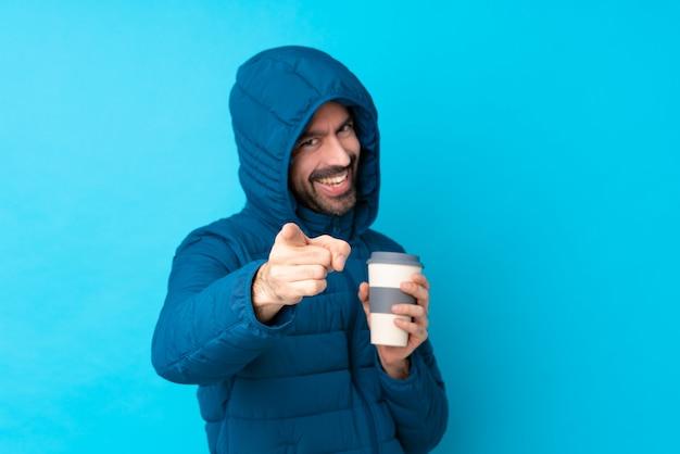 Человек, одетый в зимнюю куртку и проведение вынос кофе на изолированной синей стене указывает пальцем на вас с уверенным выражением