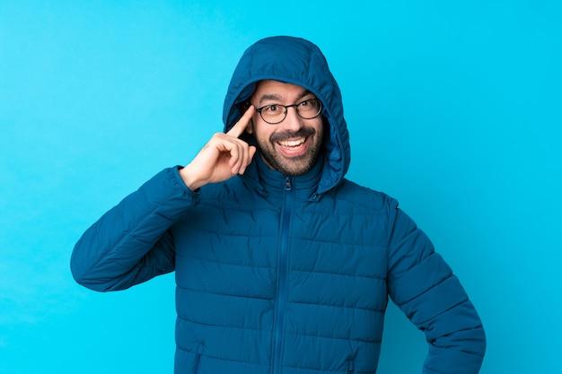 冬のジャケットを着て、眼鏡と分離の青い壁に持ち帰り用のコーヒーを保持していると笑みを浮かべて男