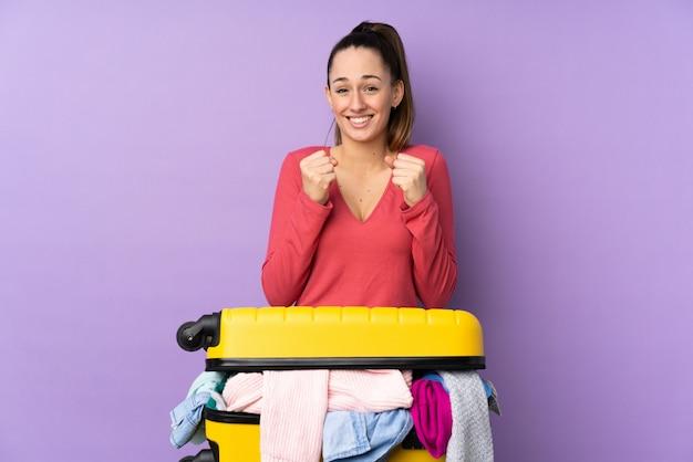 Путешественник женщина с чемоданом, полным одежды над изолированных фиолетовые стены празднует победу