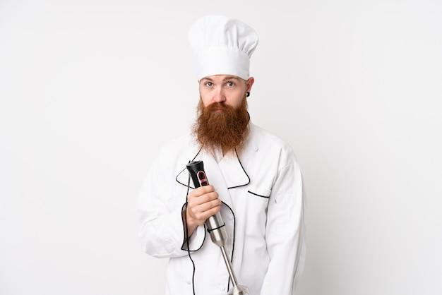 悲しい分離の白い壁にハンドミキサーを使用して赤毛の男