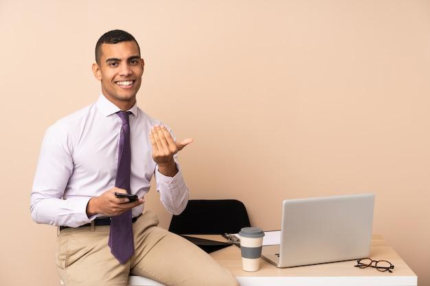Молодой деловой человек в офисе приглашает прийти