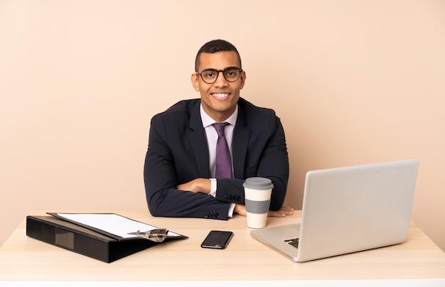 Молодой деловой человек в своем офисе с ноутбуком и другими документами, держа руки скрещенными в переднем положении