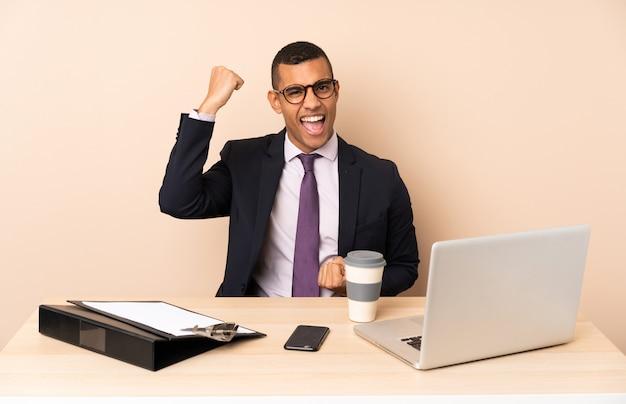 Молодой бизнесмен в своем кабинете с ноутбуком и другими документами празднует победу