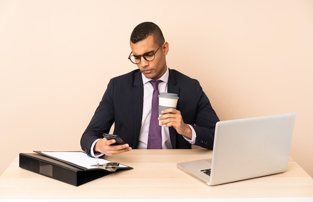 Молодой деловой человек в своем офисе с ноутбуком и другими документами, держа кофе, чтобы забрать и мобильный