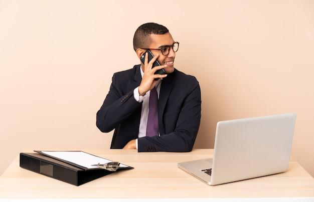 Молодой деловой человек в своем офисе с ноутбуком и другими документами, ведение разговора с мобильным телефоном с кем-то