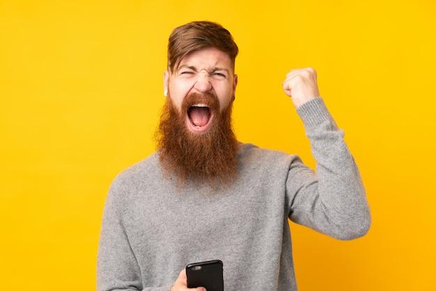 Рыжий мужчина с длинной бородой над изолированной желтой стеной с телефоном в победной позиции