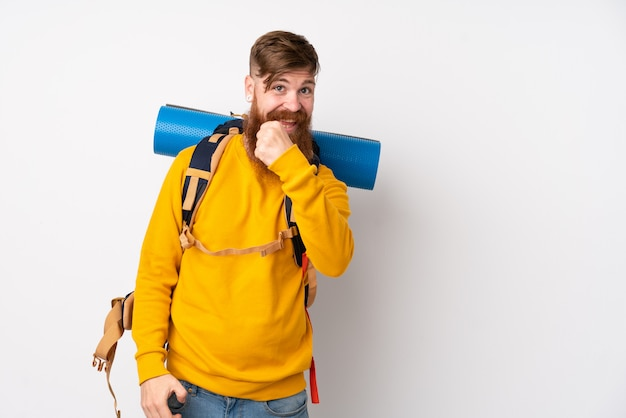 Молодой человек альпиниста с большим рюкзаком над изолированной белой стеной празднует победу