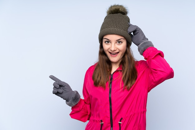 驚いたと側に指を指している青い壁に分離された冬の帽子を持つ若い女性