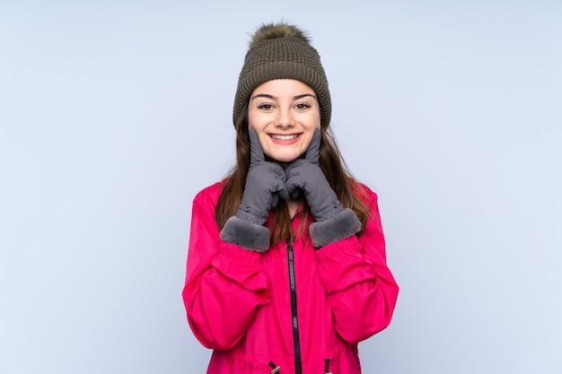 幸せで快適な表情で笑顔の青い壁に分離された冬の帽子を持つ若い女性
