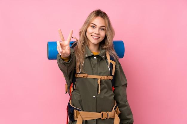 Девушка альпиниста подростка с большим рюкзаком изолированная на розовой стене усмехаясь и показывая знак победы