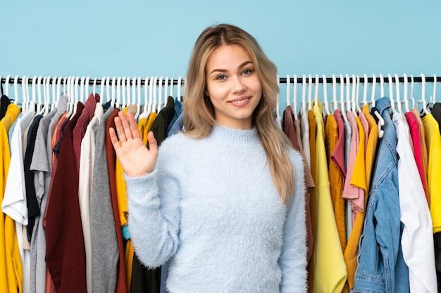幸せな表情で手で敬礼青い壁に分離されたいくつかの服を買うティーンエイジャーの女の子