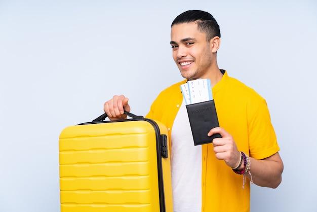 スーツケースとパスポートと休暇で青い壁に分離されたハンサムな男