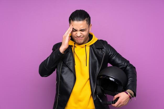 Человек с мотоциклетный шлем, изолированные на фиолетовые стены, недовольны и разочарованы чем-то. негативное выражение лица