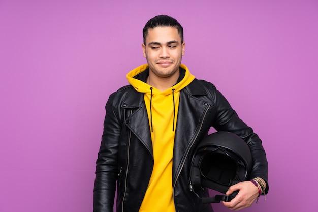 Человек с мотоциклетным шлемом, изолированный на фиолетовой стене, стоит и смотрит в сторону