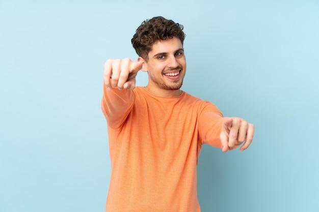 Человек, изолированный на синей стене, указывает пальцем на вас, улыбаясь