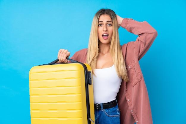 旅行スーツケースと休暇で孤立した青い壁の上の若い女性と驚いた