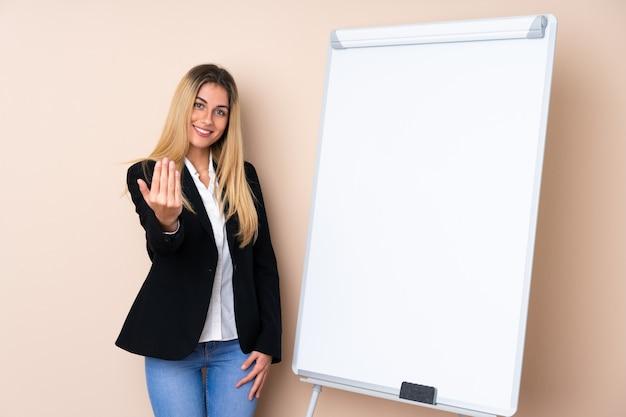 Молодая женщина дает представление на белой доске и приглашает прийти с рукой