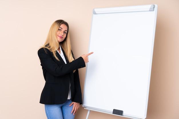 Молодая женщина, давая представление на белой доске и указывая в сторону