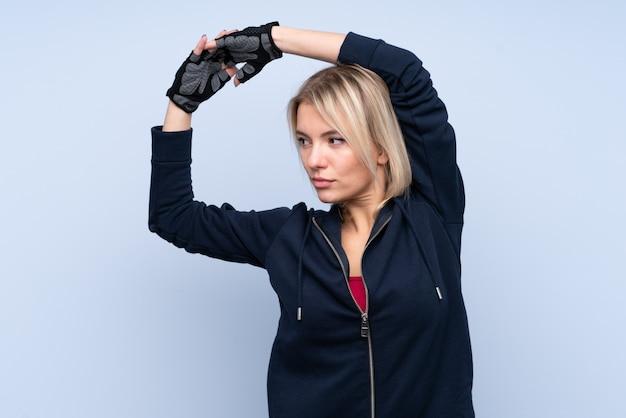 孤立した青い壁のストレッチを若いスポーツ金髪女性