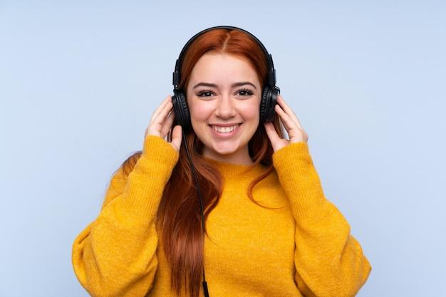 音楽を聴く分離の青い壁の上の赤毛のティーンエイジャーの女の子