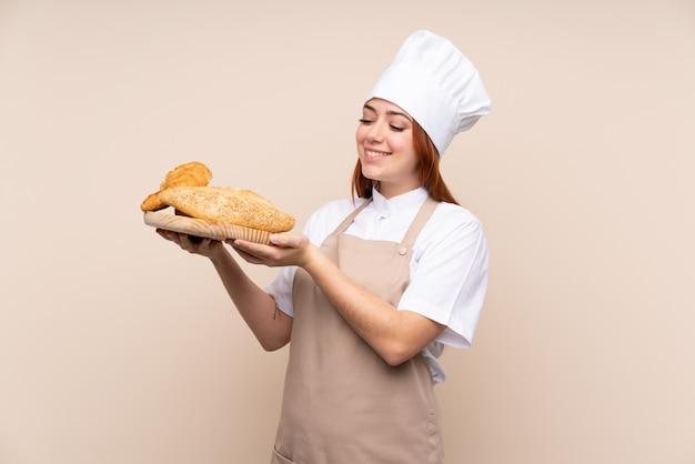 Рыжая девушка-подросток в форме шеф-повара держит стол с несколькими хлебцами с счастливым выражением
