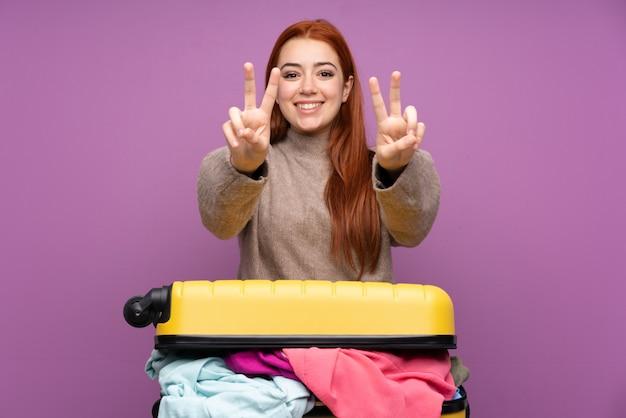 Девушка-подросток путешественник с чемоданом, полным одежды, улыбается и показывает знак победы