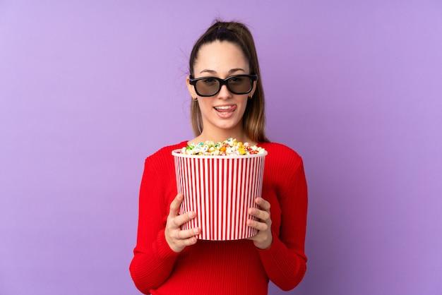 Молодая женщина держит попкорны над изолированной стеной