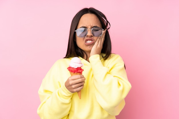 歯痛で孤立したピンクの壁にコルネットアイスクリームを置く若いブルネットの女性