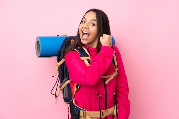 Молодая женщина альпиниста с большим рюкзаком над изолированной розовой стеной празднует победу