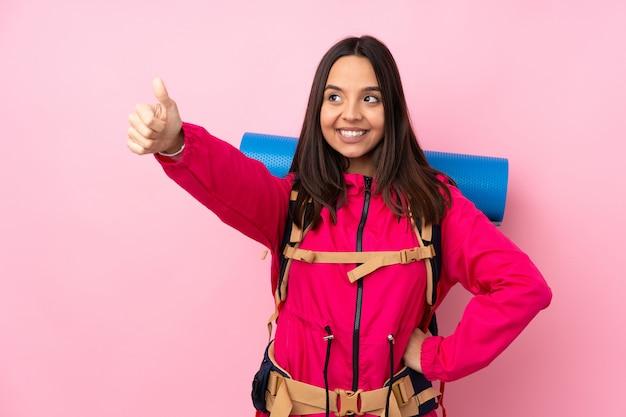 ジェスチャーを親指を与える分離のピンクの壁の上の大きなバックパックを持つ若い登山家女性