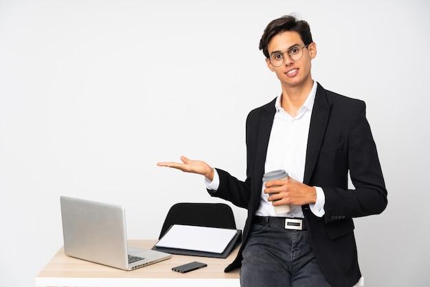 Бизнесмен в своем кабинете над изолированной стеной белая стена, протягивая руки в сторону за приглашение прийти