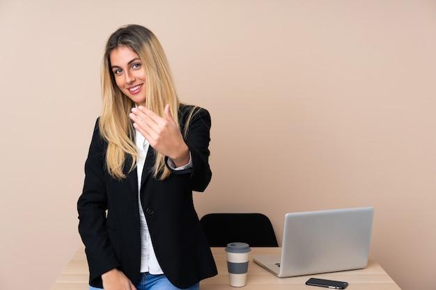 Молодая бизнес-леди в офисе приглашая прийти