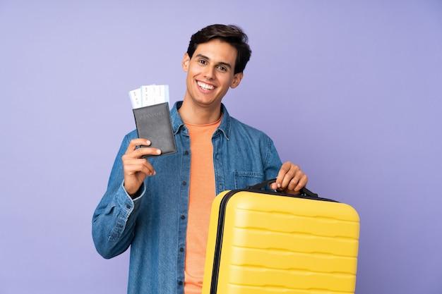 Человек над изолированной фиолетовой стеной в отпуске с чемоданом и паспортом
