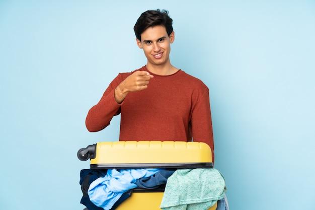 Человек с чемоданом, полным одежды, над синей стеной показывает пальцем на тебя