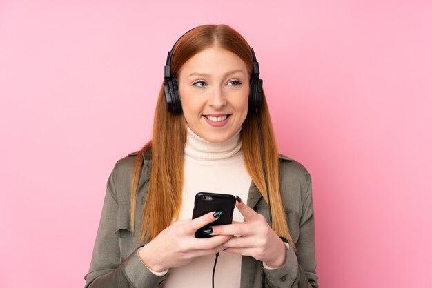 携帯電話で音楽を聴くと分離のピンクの壁の上の若い赤毛の女性と正面