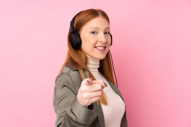 音楽を聴くと、前方を向く孤立したピンクの壁の上の若い赤毛の女性