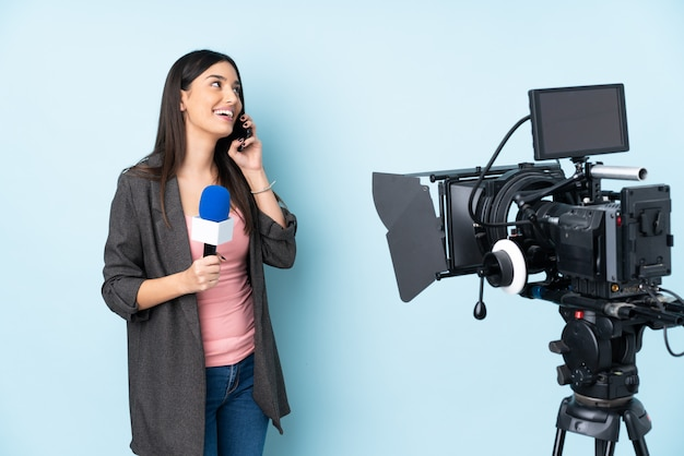 マイクを保持し、携帯電話との会話を維持する青い壁に分離されたニュースを報告するレポーター女性