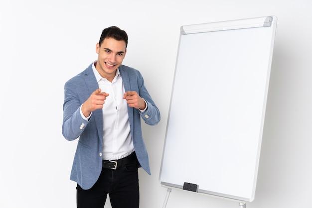 Молодой кавказской красавец, изолированные на фиолетовые стены, презентации на белой доске и указывает пальцем на вас