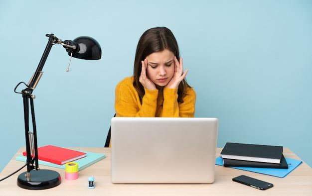 Студент девушка учится в ее доме, изолированных на синей стене с головной болью