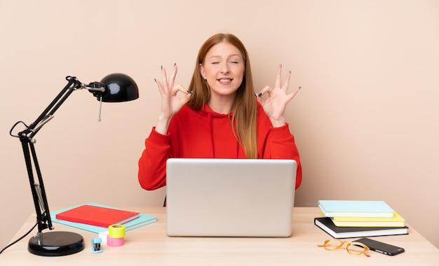 Молодой студент женщина на рабочем месте с ноутбуком в позе дзен