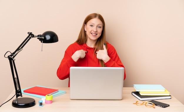驚きの表情を持つラップトップで職場の若い学生女性