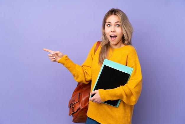 Девушка студента подростка на пурпуре удивленная и указательный палец в сторону