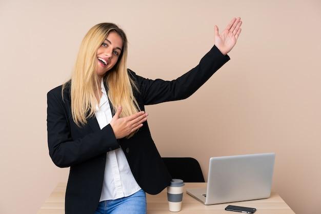 Молодая деловая женщина в офисе, протягивая руки в сторону за приглашение прийти