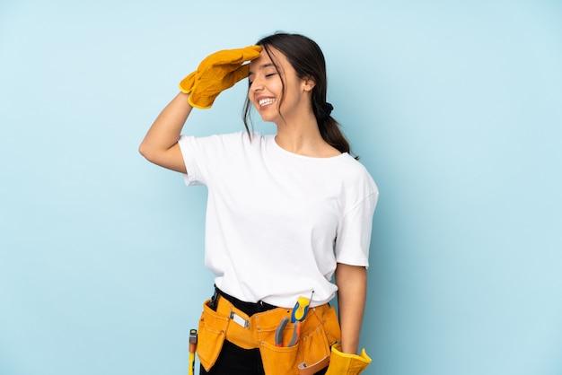 孤立した壁の上の若い電気技師の女性