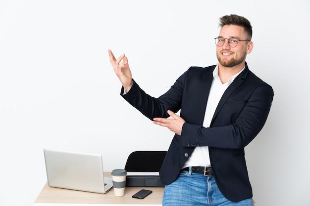 Человек в офисе изолирован на белой стене, протягивая руки в сторону за приглашение прийти