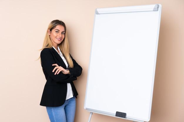 Молодая уругвайская женщина дает представление на белой доске и улыбается